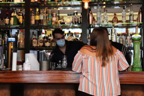 Bar staff serving customer